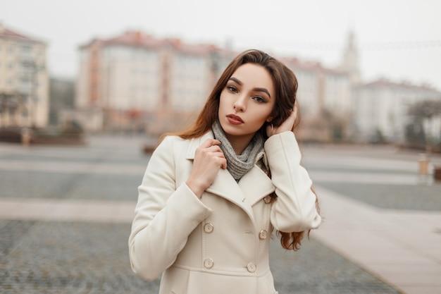 Ragazza bellissima giovane modella in cappotto di moda con un maglione in posa fuori in città in una giornata invernale Foto Premium