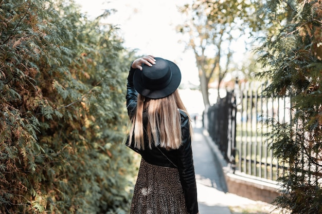 Bella giovane modella ragazza con i capelli lunghi in una giacca di pelle alla moda con un abito vintage e cappello viaggia nel parco in una calda giornata autunnale