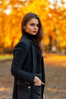 Bella ragazza modello con labbra rosse in un blazer nero alla moda con un maglione all'aperto con fogliame autunnale dorato colorato al tramonto. stile e bellezza femminili eleganti