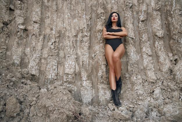 Bellissima modella giovane con capelli scuri e labbra rosse in piedi tra una cava di sabbia asciutta e guardando direttamente con sguardo penetrante.