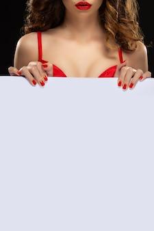 Bello giovane modello con le labbra rosse e il manicure rosso tiene la bandiera bianca