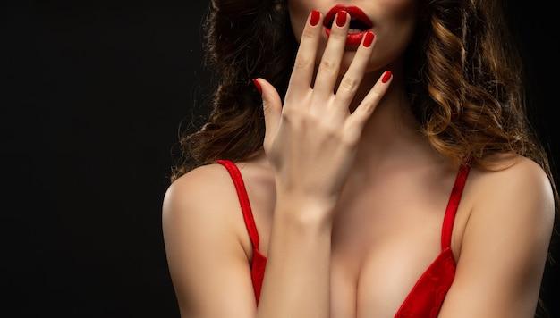 Bello giovane modello con labbra rosse e manicure rossa