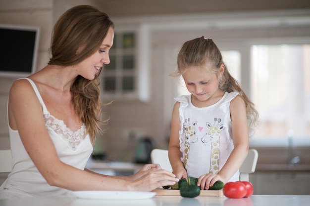 Bella giovane mamma e piccola figlia divertirsi e preparare le verdure per insalata in una cucina bianca in un interno in stile scandinavo.
