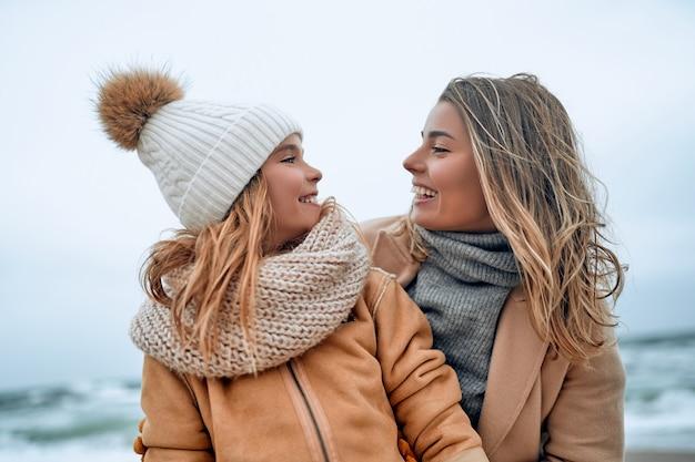 La bella giovane madre in un cappotto si diverte con la sua graziosa figlia sulla spiaggia in inverno.