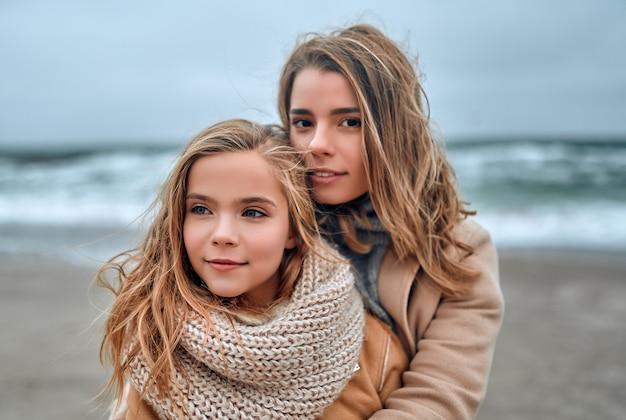 Bella giovane madre in un cappotto con la sua graziosa figlia carina sulla spiaggia in inverno.