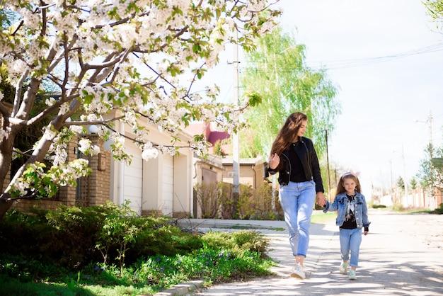 Bella giovane madre e la sua adorabile figlia piccola, carina bambina riccia che gioca e cammina in giardino in una soleggiata giornata primaverile.