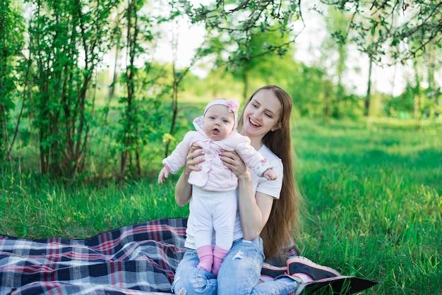 La bella giovane madre sta tenendo la piccola figlia nel parco estivo. concetto di infanzia e maternità
