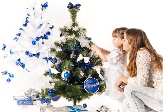 Bella giovane madre e piccola figlia affascinante decorano un albero di natale con giocattoli blu e bianchi su sfondo bianco.