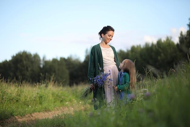 Bella giovane madre con figlia che cammina su una strada rurale