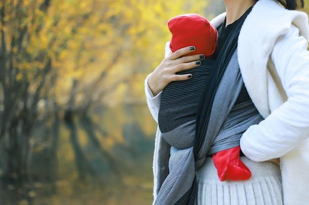 Bella giovane madre con il suo bambino neonato in imbracatura outdoor babywearing concept