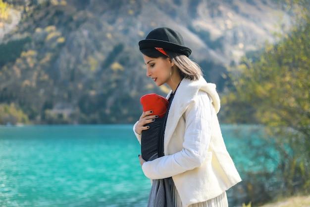 Bella giovane madre con il suo bambino neonato in imbracatura all'aperto madre che porta il suo bambino e viaggia