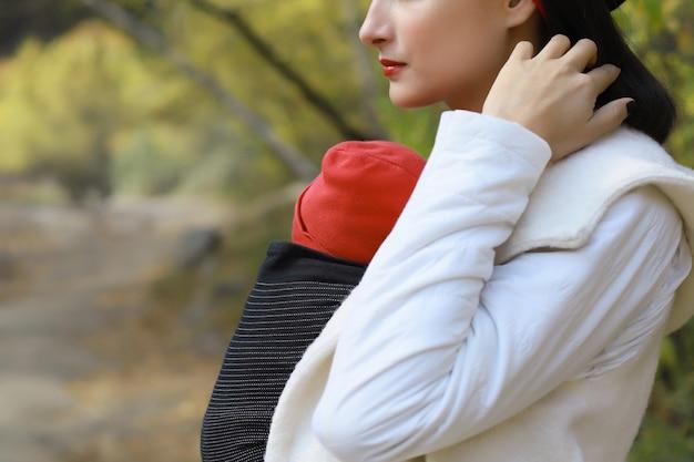 Bella giovane madre con il suo bambino in fascia all'aperto la donna sta portando il suo bambino e cammina