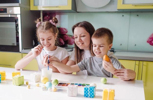 Una bella giovane madre con due bambini ha decorato le tradizionali uova di pasqua con vernice brillante il concetto di una famiglia felice che si prepara per le vacanze di pasqua