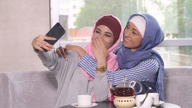 Le belle giovani ragazze musulmane fanno selfie su uno smartphone