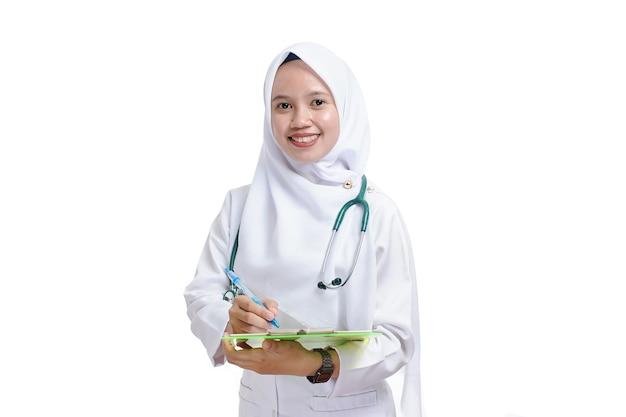 Bella giovane donna musulmana infermiera o medico azienda appunti isolati su sfondo bianco