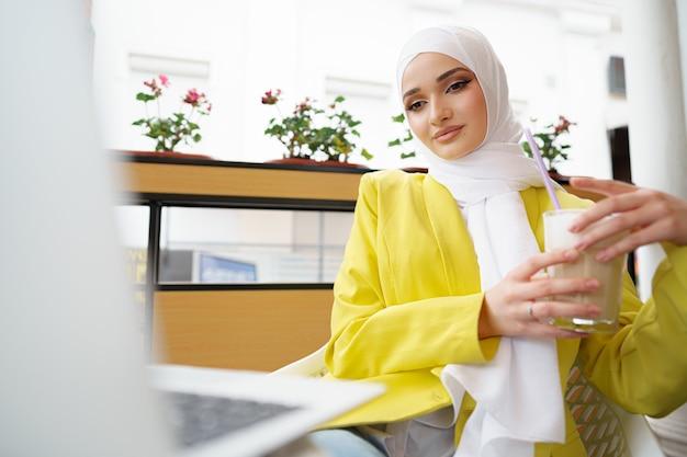 Bella giovane donna musulmana che usa il computer portatile mentre è seduta al bar