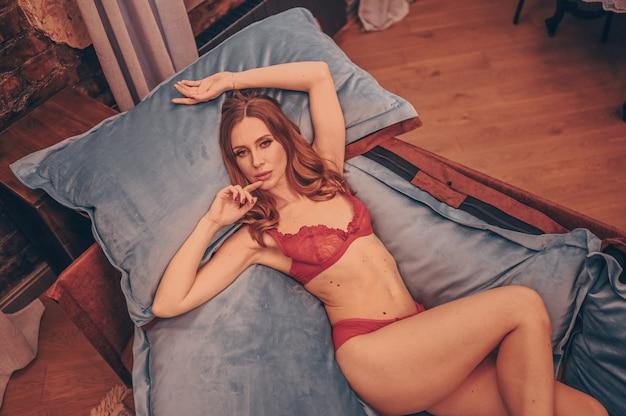 Bella giovane bellezza naturale sexy mezza donna nuda sdraiata sul divano con cuscini blu in pizzo rosso