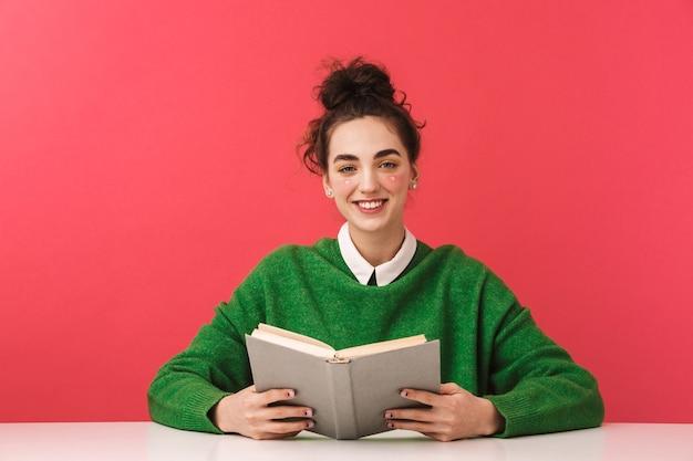 Bella giovane studentessa nerd ragazza seduta al tavolo isolato, studiando con i libri,