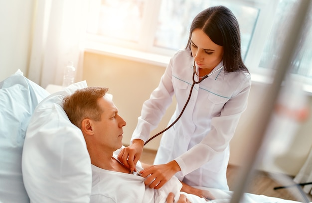Una bellissima giovane infermiera con uno stetoscopio esamina un paziente maturo che giace su un letto in un reparto moderno.