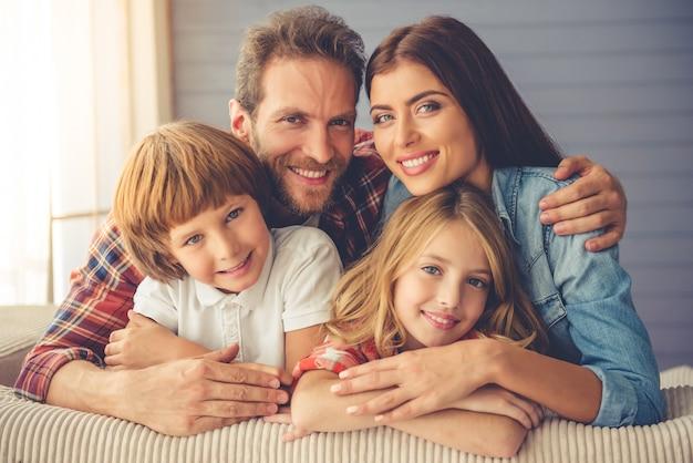 Bellissimi giovani genitori e i loro figli si abbracciano