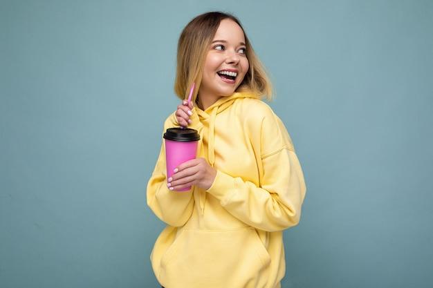 Bella giovane donna bionda positiva che indossa abiti casual alla moda isolati su sfondo colorato parete che tiene tazza di carta per mockup bere caffè guardando di lato.