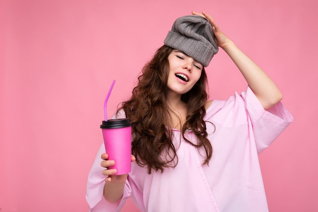 Bella giovane donna riccia bruna positiva che indossa camicia rosa e cappello grigio