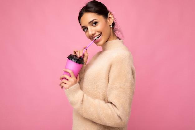 Bella giovane donna bruna positiva che indossa abiti casual eleganti isolati su sfondo colorato muro che tiene tazza di carta per mockup bere caffè guardando la fotocamera.