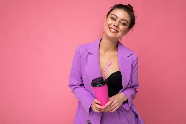 Bella giovane donna bruna positiva che indossa abiti casual alla moda isolati su sfondo colorato