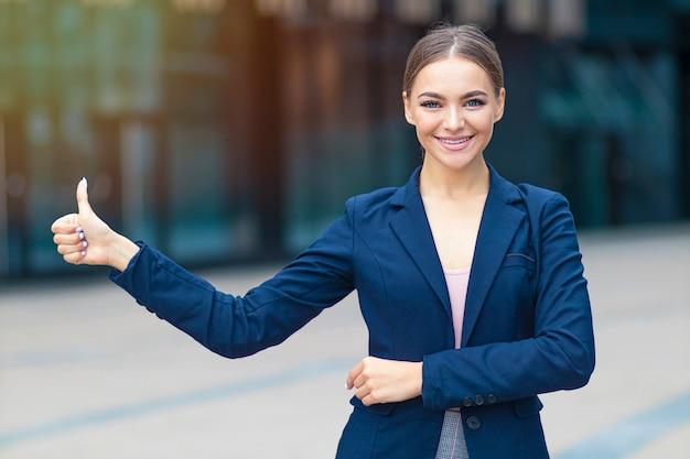 Bella giovane donna di affari positiva in vestito