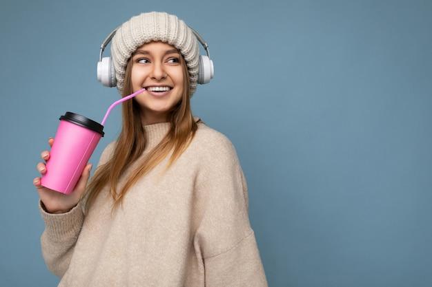 Bella giovane donna bionda sorridente positiva che indossa il maglione beige del cappello lavorato a maglia e wireless bianco