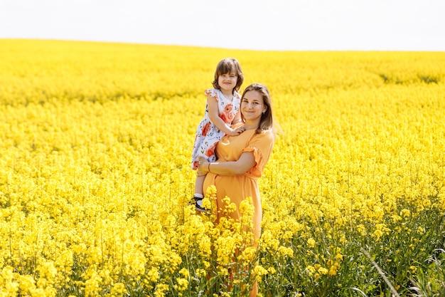 Una bella giovane mamma incinta e la sua piccola figlia in un campo di colza giallo.