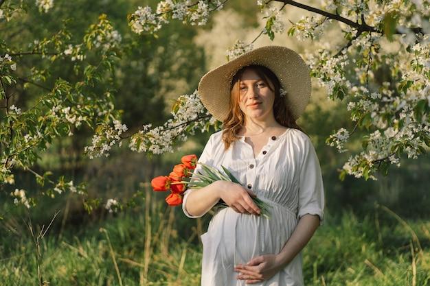 Una bella giovane donna incinta in un abito bianco cammina nel giardino primaverile