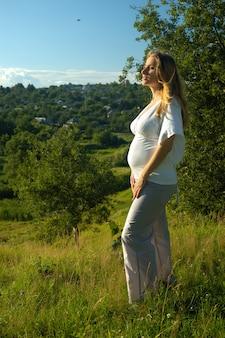 Bella giovane donna incinta con una pancia nuda in piedi al prato. gravidanza nella natura del colore, si gode la calda natura estiva