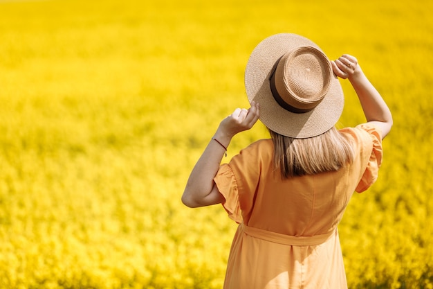 Bella giovane donna incinta in un campo di colza giallo.