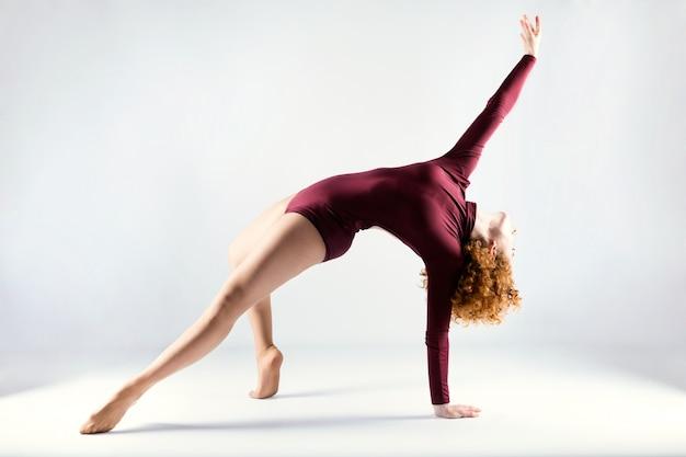 Bella giovane ballerina professionista danza su sfondo bianco.