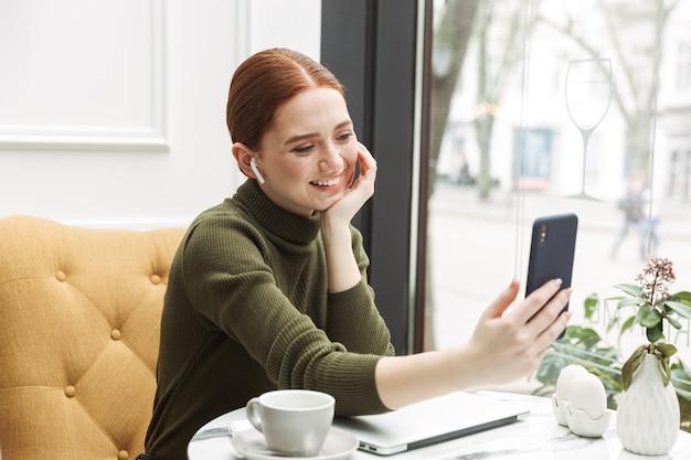 Bella giovane donna dai capelli rossi che si rilassa al tavolino del bar al chiuso, beve caffè, lavora al computer portatile, fa una videochiamata