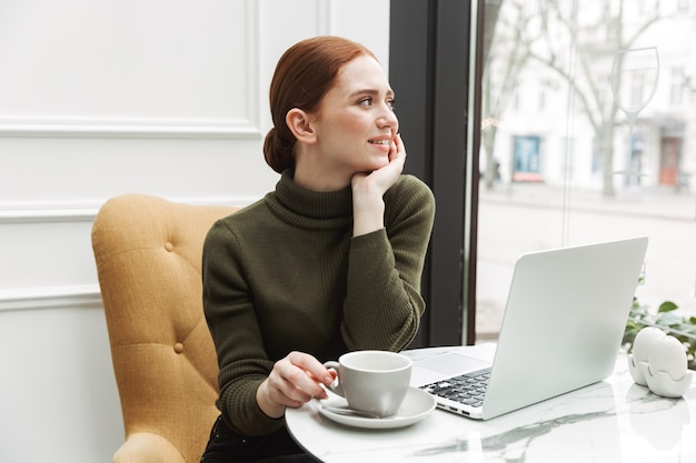 Bella giovane donna dai capelli rossi che si rilassa al tavolino del bar al chiuso, beve caffè, lavora al computer portatile