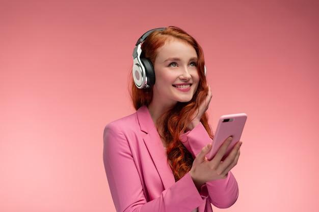 Bella giovane donna della testarossa con le cuffie che ascolta la musica sul telefono astuto