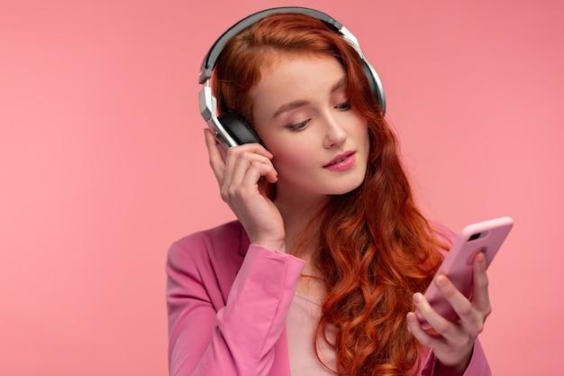 Bella giovane donna della testarossa con le cuffie che ascolta la musica su smart