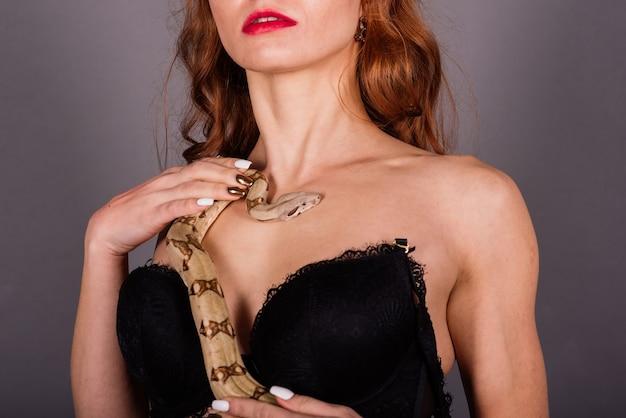Bella giovane donna della testarossa con il serpente con un trucco perfetto alla moda