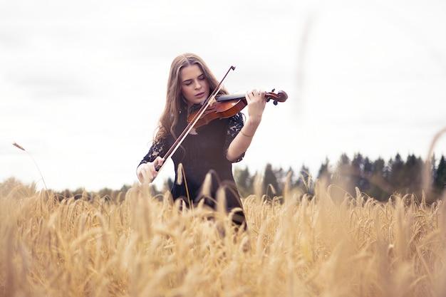 Bella giovane donna triste in piedi su un campo di grano con entusiasmo a suonare il violino