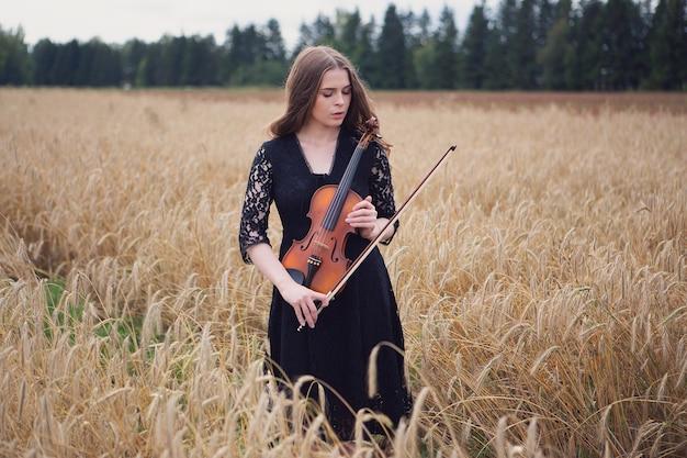 Bella giovane donna triste in piedi su un campo di grano preme un violino