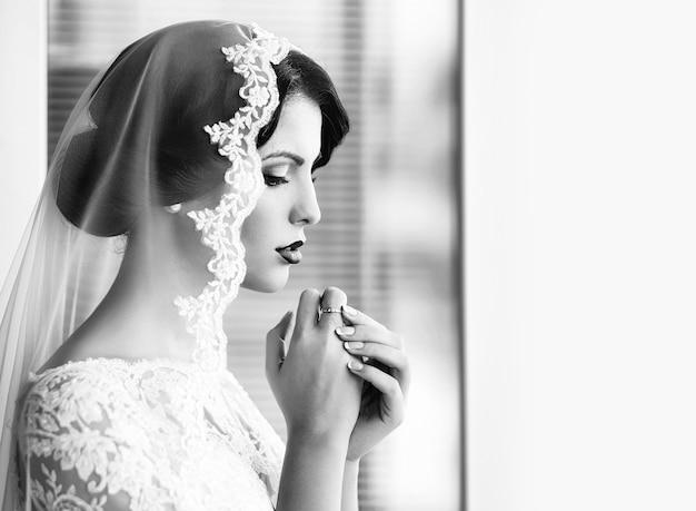 Bella giovane sposa sensuale in abito di pizzo bianco e velo sulla testa che tengono le mani vicino al viso.
