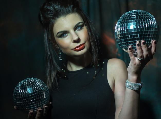 Bella giovane donna sensuale che tiene le palle da discoteca