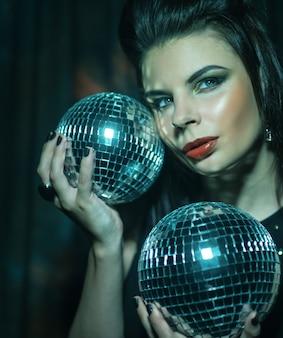 Bella giovane donna sensuale che tiene le palle da discoteca Foto Premium
