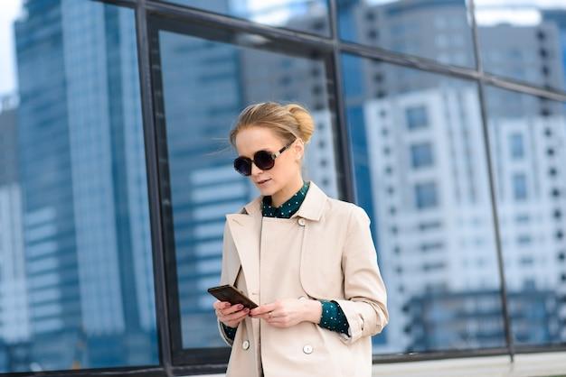 Bella giovane donna d'affari caucasica seria con gli occhiali mentre si cammina durante una pausa in città.