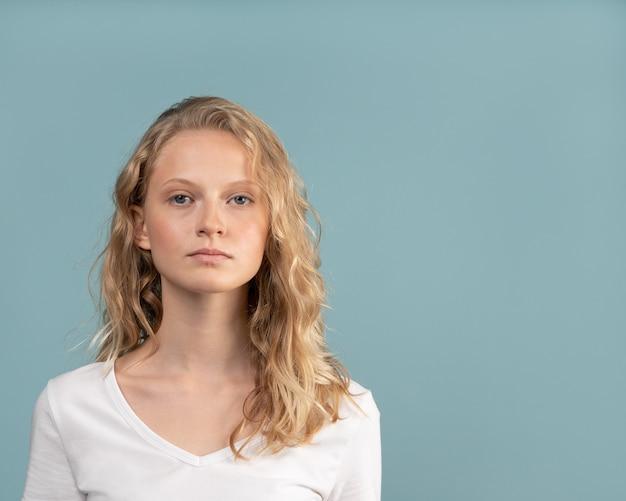 Bella giovane donna bionda intelligente seria senza trucco sul tono neutro di colore