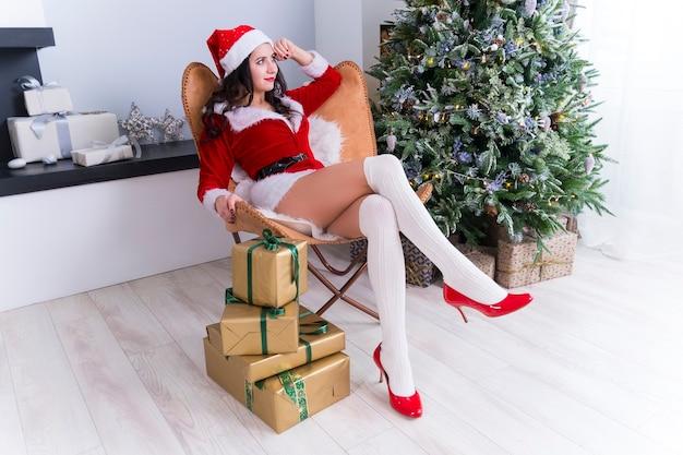 Bella giovane donna sessuale vestita in costume di babbo natale seduto sull'accogliente poltrona accanto all'albero di natale con regali la mattina presto. luce brillante della foto accogliente di natale dalla finestra.