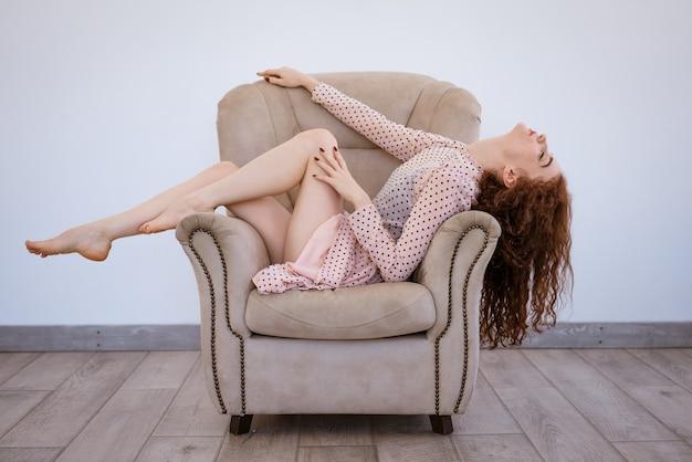 Bella giovane donna dai capelli rossi snella sdraiata su una sedia alzando lo sguardo