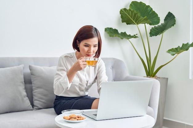 Bella giovane donna asiatica sorridente che lavora al computer portatile e che beve caffè in salotto a casa.